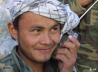An Afghan soldier smiles as he listens to the radio