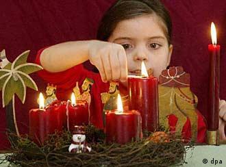Ein Mädchen zündet die vierte Kerze eines Adventskranzes an (21.12.2004/dpa)