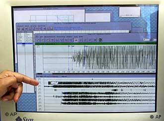 scientist points to a seismograph reading from an earthquake
