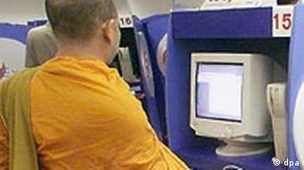 A Thai monk looking at a computer screen