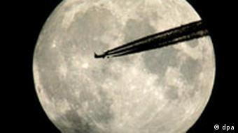 Ein Flugzeug fliegt am Montag (30.08.2004) über Oberfranken vor dem hell leuchtenden Vollmond vorbei. Die Kondenzsteifen erscheinen im Mondlicht durch die Unterbelichtung schwarz. Foto: dpa
