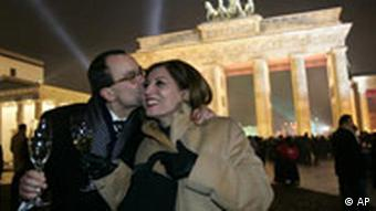 Two people kiss in front of the Brandenburg Gate