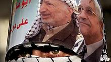 A masked Fatah activist weas a kaffiyeh, the traditional Arab headdress, topped with a poster of interim Palestinian leader and presidential front-runner Mahmoud Abbas, right, and late Palestinian leader Yasser Arafat during a rally commemorating the 40th anniversary of the Fatah movement in the village of Yetma near the West Bank city of Nablus, Saturday, Jan. 1, 2005. (AP Photo/Majdi Mohammed)