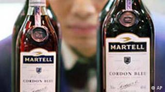 A shop assistant looks at bottles of imported cognac at a Beijing department store Monday, February 26, 1996. Sales of foreign liquor have been hit hard by a ban on wining and dining by government officials at public expense. Before the ban up to 90 percent of foreign liquor was bought by officials, who used it for gifts or banquets then claimed the expense from their work units. (AP Photo/Greg Baker)