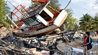 A woman trys to sort out what to do with a boat that landed on and destroyed her house in Ban Nam Khem