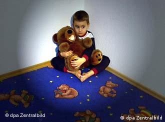Young boy sits in the corner with a stuffed bear