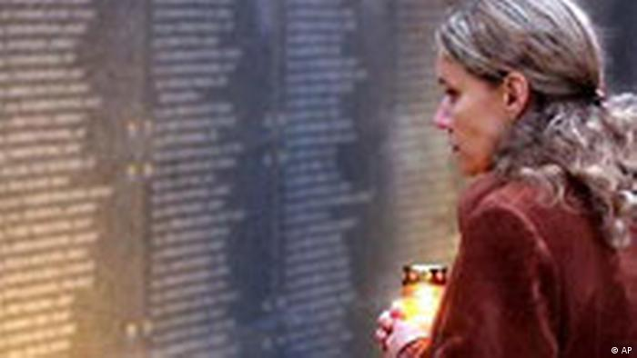 A woman holds a candle as she reads names of insurgents on a memorial wall at the Warsaw Uprising Museum in Warsaw