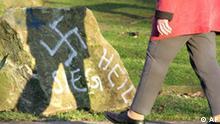 Ein Frau laeft am Montag, 10. Januar 2005, in der Abendsonne an einem mit Nazi-Parolen beschmierten juedischen Gedenkstein auf einem Friedhof in Dortmund vorbei. Mehrere Grabsteine wurden mit Hakenkreuzen und SS-Symbolen beschmiert. (AP Photo/Martin Meissner) -----A woman passes by a Jewish memorial , desecrated with Nazi symbols, at a cemetery in Dortmund, Germany, Monday, Jan. 10, 2005. Swastikas and racist slogans were sprayed on some gravestones. (AP Photo/Martin Meissner)