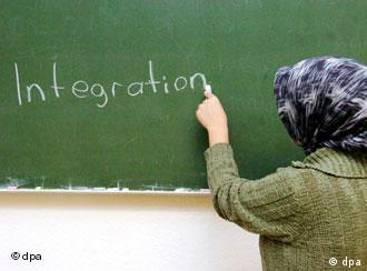 A woman in a headscarf writes integration on a chalk board