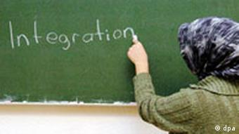 Woman writes the word integration on a chalk board