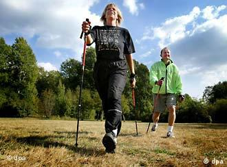 Eine Frau und ein Mann, die Nordic Walking machen