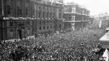 Crowds of civilians, British and Allied troops wave and cheer as Winston Churchill, second balcony from left, and members of the cabinet appear, to celebrate the end of the war in Europe, in Whitehall, London, May 8, 1945. (AP Photo)