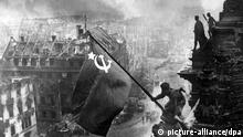 Soviet soldier waves the Soviet flag over the Reichstag (picture-alliance/dpa)