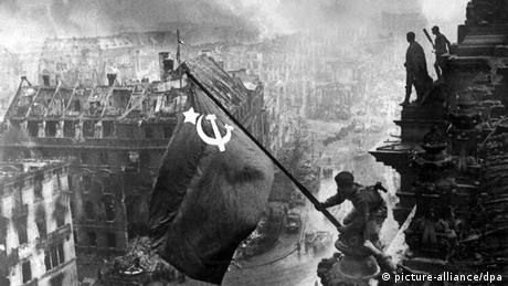 Black and white photo of two Soviet soldiers hoisting a flag on the Reichstag in Berlin (picture-alliance/dpa)