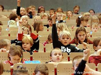 Schoolchildren sitting in a university lecture hall raise their hands to answer a question
