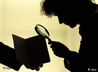 A person studies an open book with a magnifying glass