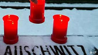 A man places a candle on the sign reading Auschwitz