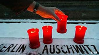 A candle is being placed at a loading ramp of former German railway company Deutsche Reichsbahn in Berlin to remember the Holocaust victims on the 60th anniversary of the liberation of the Nazi-era Auschwitz death camp
