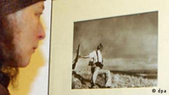 Eine Besucherin betrachtet am Freitag (21.01.2005) in Berlin eine der wohl berühmtesten Aufnahmen des Fotografen Robert Capa, den Tod eines spanischen Milizionärs vom 05. September 1936 an der Front von Cordoba. 50 Jahre nach dem Tod des in Ungarn geborenen legendären Kriegsreporters sind 300 seiner Fotografien vom 22. Januar bis zum 18. April im Martin-Gropius-Bau in Berlin zu sehen. Foto: Stephanie Pilick dpa/lbn +++(c) dpa - Report+++
