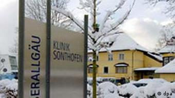 A large sign and a hospital building in the background, all covered in snow