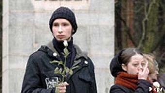 Gedenken auf dem Heidefriedhof in Dresden, junge Leute mit weißen Rosen