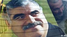 A man puts a poster of slain former Lebanese Prime Minister Rafik Hariri in the window of his car in Beirut, Lebanon Tuesday, Feb. 15, 2005. A stunned nation plunged into deep mourning Tuesday for Hariri, whose assassination in a massive bomb blast Monday raised fears that the country might revert to the political violence of the 1975-90 civil war. (AP Photo)