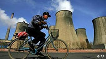 A man cycles past cooling towers of the coal powered Fuxin Electricity Plant in Fuxin, in China's northeast Liaoning province