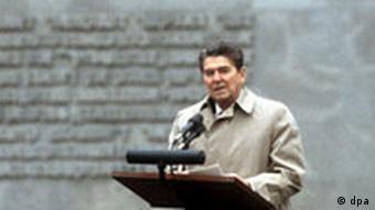 Ronald Reagan während seiner Ansprache am 5. Mai 1985 in Bergen-Belsen. Im Rahmen des Staatsbesuchs des amerikanischen Präsidenten in Deutschland, besuchten Ronald Reagan und Bundeskanzler Helmut Kohl am 5. Mai 1985 die Gedenkstätte für die Opfer des Nazi-Regimes in Bergen-Belsen. Bei seiner Rede versprach der US-Präsident den Überlebenden der Konzentrationslager, die Opfer des Nazi-Terrors niemals in Vergessenheit geraten zu lassen.