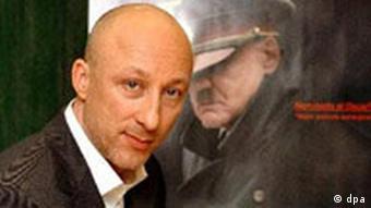 Director Oliver Hirschbiegel against a poster showing Adolf Hitler