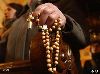 A priest holds rosary beads