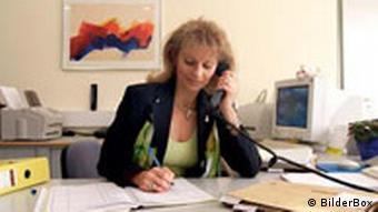 Frau im Büro mit Telefon