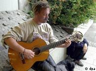 Hombre sin casa, toca la guitarra para ganar algo de dinero.