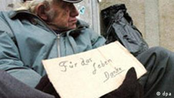 A man sits on the street begging and holding a sign