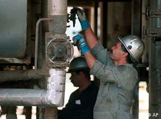 An Iranian oil worker opens a valve on a pipe at a oil refinery in Tehran