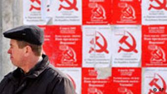 A Moldovan man waits for a bus in front of electoral posters advertising the Communists party in Chisinau Moldova