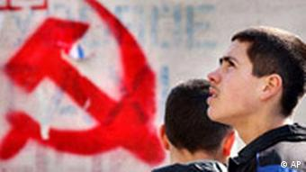 Moldovan youths pass by the symbol of the Communists party in Chisinau Moldova