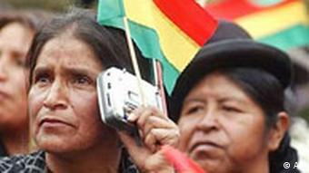 An Andean woman listens to the news using a small radio