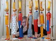 Artista plástico Stefan Hempel coloca o braço em um de seus coelhos de madeira em seu ateliê em Stralsund. Os coelhos da Páscoa de 80 centímetros de altura são algumas das divertidas figuras que Hempel fabrica para a venda em galerias de todo o país