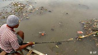 A villager fishes for his dinner in a polluted river in Bali
