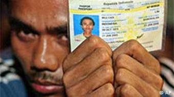 An Indonesian migrant worker holds his identity card