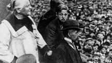 Clara Zetkin fordert auf einer Kundgebung zur Durchführung der Revolution nach russischem Muster auf (Ort und Datum leider unbekannt). Die am 5. Juli 1857 in Wiederau geborene und am 20. Juni 1933 in Archangelskoje bei Moskau verstorbene Politikerin schloß sich 1878 der Sozialdemokratie an, baute die Frauenbewegung auf und war von 1891-1917 Herausgeberin der Frauenzeitschrift Die Gleichheit. Zetkin war Mitbegründerin des Spartakusbundes (1916) und der USPD (1917). Von 1920 bis 1933 war sie für die KPD Mitglied des Reichstages. Den Internationalen Frauentag, von der SPD 1914 auf den 8. März festgelegt und nach mehrfachen Unterbrechungen 1980 wiederbelebt, hatte sie 1911 initiiert.