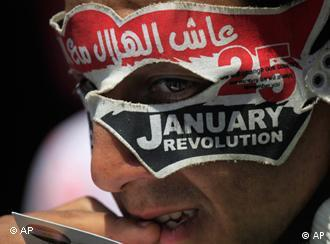 An Egyptian puts on a mask in support of the revolution