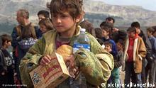 ARCHIV - Ein Junge aus dem Kosovo trägt Lebensmittel weg, die er im Flüchtlingslager in Stenkovac in Mazedonien erhalten hat (Archivfoto vom 11.04.1999). Nachdem jugoslawische Truppen im Frühjahr 1999 die Vertreibung der Kosovo-Albaner fortsetzten, begann die NATO am 24. März 1999 den Luftkrieg gegen Jugoslawien. 79 Tage dauerten die Angriffe ohne UN-Mandat. Foto: Gouliamaki (zu dpa-Themenpaket Zehnter Jahrestag der NATO-Bombardierung Jugoslawiens am 17.03.2009) +++(c) dpa - Bildfunk+++
