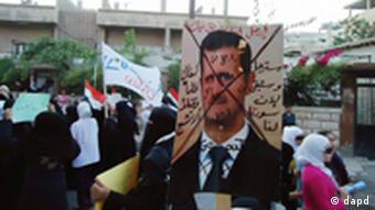Demonstrierende Frauen in Syrien hinter einem Plakat, auf dem das Konterfei von Präsident Assad durchgestrichen wurde (Foto: dapd)