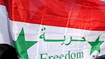 Syrian women stand behind their national flag with the word Freedom on it