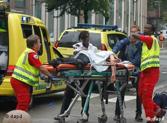 A victim is carried to a waiting ambulance in central Oslo, Friday July 22, 2011, following an explosion that tore open several buildings including the prime minister's office, shattering windows and covering the street with documents.(Foto:Berit Roald, Scanpix, Norway/AP/dapd) NORWAY OUT: