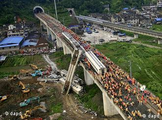 Chinese rescuers work around the wreckage of train cars in Wenzhou in east China's Zhejiang province, Sunday, July 24, 2011. A bullet train crashed into another high-speed train, killing dozens of people and once again raising safety concerns about the country's fast-expanding rail network. (Foto:Color China Photo/AP/dapd) CHINA OUT