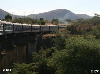 A train passing alongside a mountain