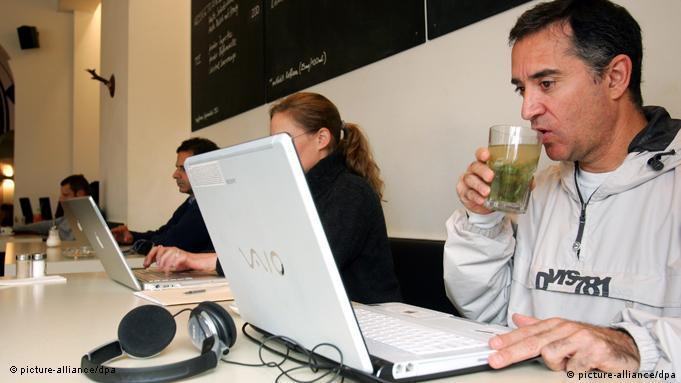 A man works on his laptop and drinks a cupe of tea as he sits next to others in a cafe.