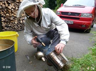 A beekeeper wearing a veiled hat is burning formic acid in a metal jug. (photo: dw)
